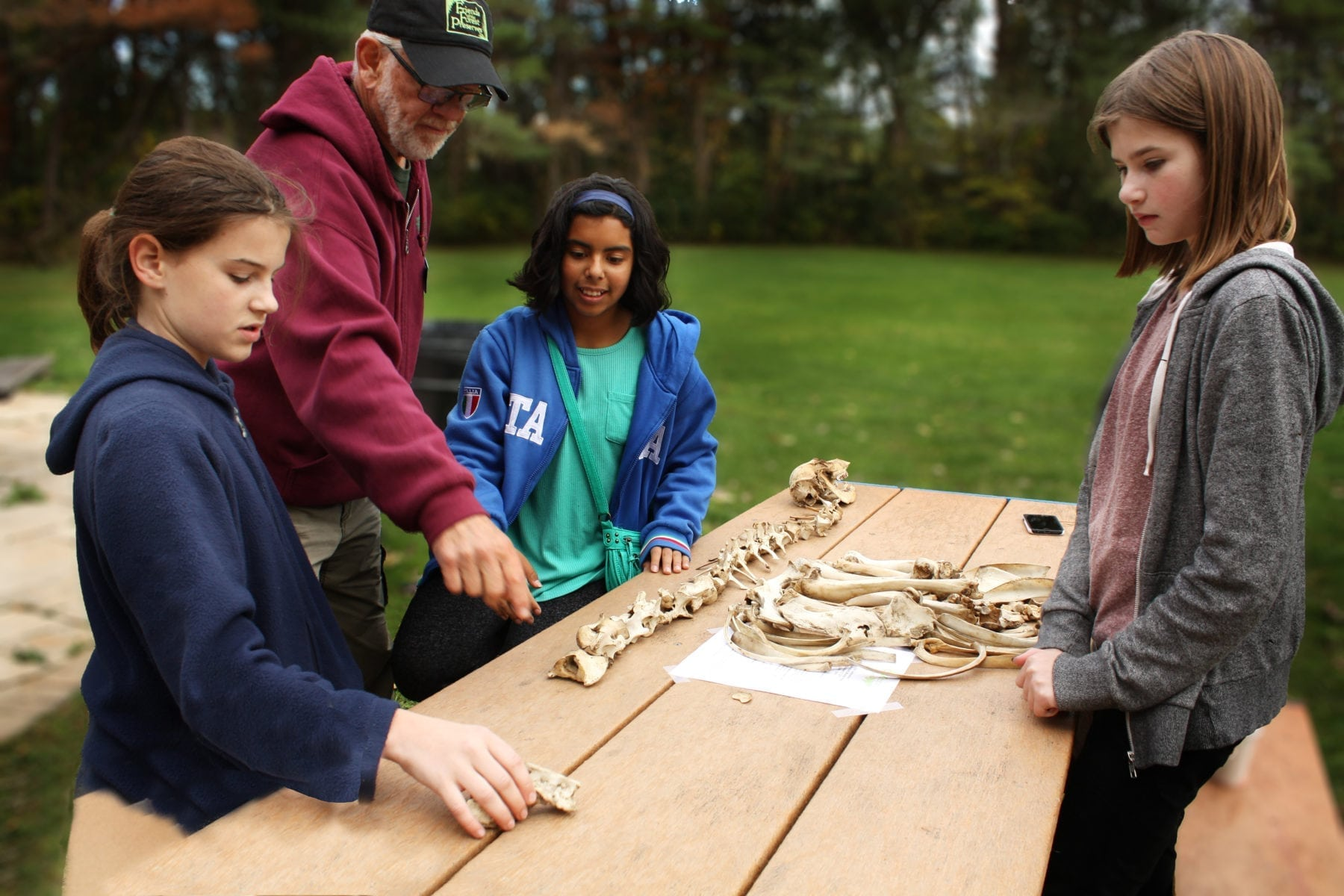 middle school students learning about animal bones at backyard nature center